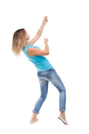 woman rope: back view of standing girl pulling a rope from the top or cling to something. girl  watching. Rear view people collection.  backside view of person.  Isolated over white background. blonde in a blue shirt and jeans, he pulls the top rope for turning right Stock Photo