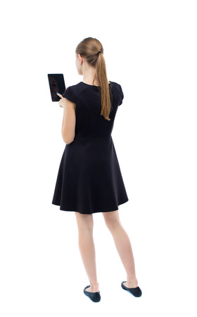 woman back: back view of standing young beautiful  girl with tablet computer in the hands of. girl  watching. Rear view people collection.  backside view of person.  Isolated over white background. The blonde in a black dress presses a finger on the screen of your sm Stock Photo