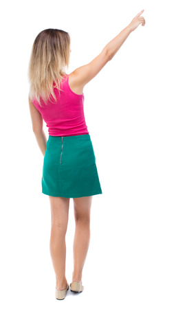 girl pointing: Back view of  pointing woman. beautiful girl. Rear view people collection.  backside view of person.  Isolated over white background.  Girl in a green skirt shows the right hand to the sky. Stock Photo