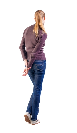 waits: back view of standing young beautiful  blonde woman. girl in jeans and sweater watching.shy girl waits. Rear view people collection.  backside view of person.  Isolated over white background. Stock Photo