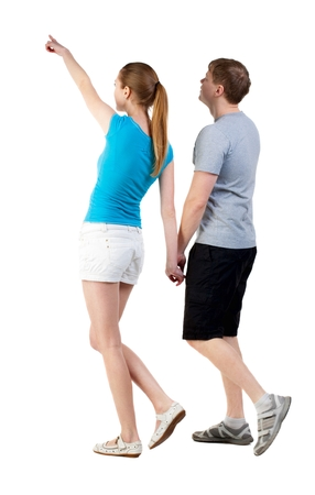 treading: Back view of walking young couple (man and woman) pointing. curious wife shows her husband attractions. Rear view people collection. backside view of person. Isolated over white background