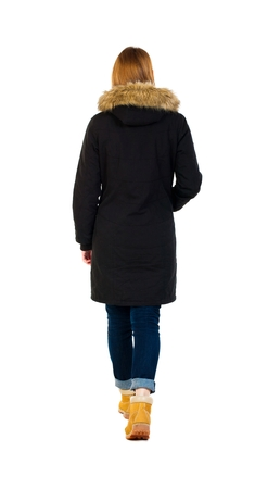 striding: Back view of going  woman in parka.