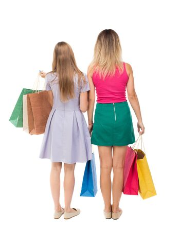 cute lady: back view of  two women  with shopping bags. backside view of person.  Rear view people collection. Isolated over white background.Young girls in colorful dresses with shopping.