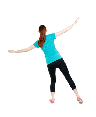 balances: Back view woman Balances waving his arms.   Standing young girl in parka. Rear view people collection.  backside view of person.  Isolated over white background. Sports girl is balancing on the rope. Stock Photo