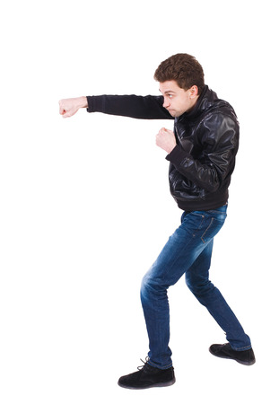 wimp: skinny guy funny fights waving his arms and legs. Isolated over white background. Man shoots with his right hand. Curly boy skillfully punches. Stock Photo