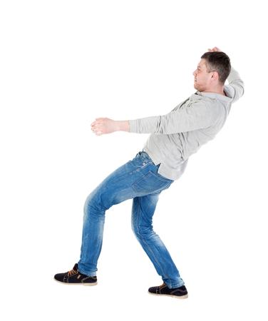 hombre cayendo: Equilibrio joven o esquivar la caída del hombre. Vista posterior recogida de las personas. trasero vista de la persona. Aislado sobre fondo blanco. El hombre sopla el viento. Hombre que hace pivotar en su pierna izquierda y tratando de no caer de nuevo. Foto de archivo