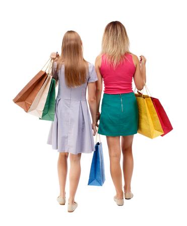 persona caminando: Vista trasera de dos mujeres caminando con bolsas de la compra. trasero vista de la persona. Vista posterior recogida de las personas. Aislado sobre fondo blanco. Las chicas jóvenes en vestidos de colores con las compras desaparecen.