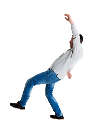 Back view man Balances waving his arms. Rear view people collection. backside view of person.  Isolated over white background. A guy in a gray jacket slipped