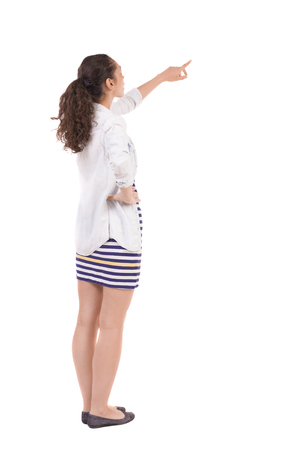 pointing at: Back view of  pointing woman. beautiful girl. Rear view people collection.  backside view of person.  Isolated over white background.Girl in a striped skirt points finger up.