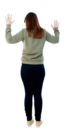back view of woman  protects hands from what is falling from above. woMan holding a heavy load Rear view people collection.  backside view of person.  Isolated over white background.  A girl in a gray sweater raised her hands in surrender