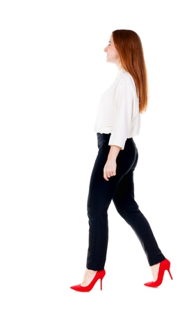 treading: walking redhead business woman. back view. going young girl in  suit. Rear view people collection.  back side view of person.  Isolated over white background. Stock Photo
