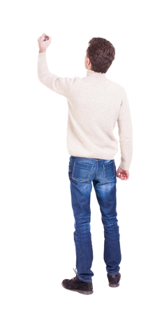 from side: back view of writing man in a white knit sweater. Young man in jeans draws. Rear view people collection.  backside view of person. Isolated over white background.