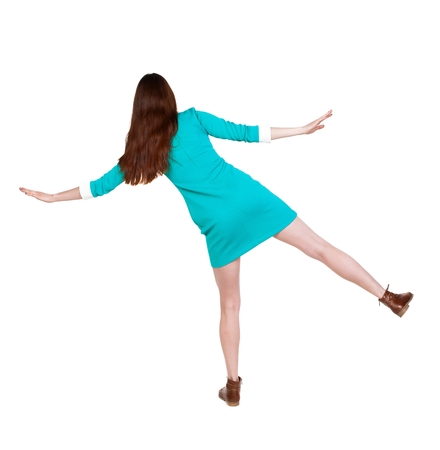 balances: Back view woman Balances waving his arms.   Standing young girl in dress. Stock Photo