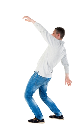 balances: Back view man Balances waving his arms. Rear view people collection. backside view of person.  Isolated over white background. A guy in a gray jacket at the time of the fall. Stock Photo