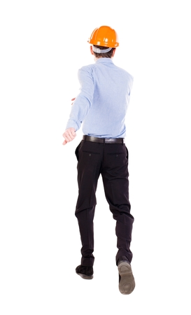 observes: Back view of running engineer in helmet. Walking guy in motion. Rear view people collection. Backside view of person. Isolated over white background. Foreman runs toward the building.