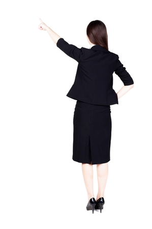 businesswoman suit: Back view of young brunette business woman pointing at wall. beautiful girl in dark suit. Rear view people collection. backside view of person. Isolated over white background. Stock Photo