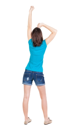 hitchhiking: Back view of  joyful woman celebrating victory hands up. Rear view people collection. backside view of person. Isolated over white background. slender brunette in a jeans shows the symbol of success or hitchhiking