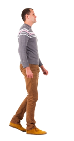 treading: Back view of walking   man in sweater and brown jeans.   young guy in jeans and  jacket. Rear view people collection.  backside view of person.  Isolated over white background.