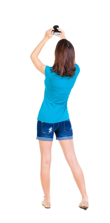 compact camera: young woman in shorts photographed something compact camera. Isolated over white background. Stock Photo