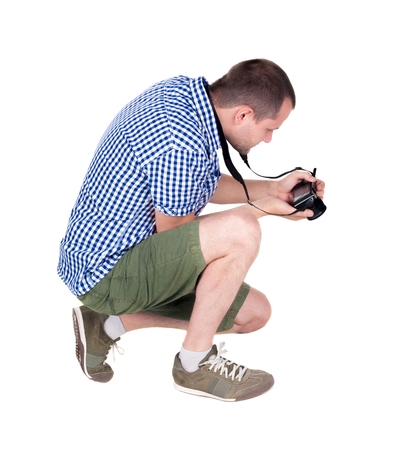 backside: Back view of man photographing.  photographer in shorts. Rear view people collection.  backside view of person.  Isolated over white background.