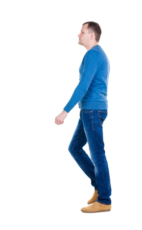 treading: Back view of going  handsome man in blue pullover. walking young guy . Rear view people collection.  backside view of person.  Isolated over white background. Stock Photo