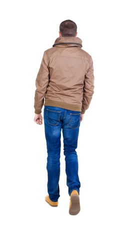 treading: Back view of going  handsome man in brown wind breaker. walking young guy . Rear view people collection.  backside view of person.  Isolated over white background. Stock Photo