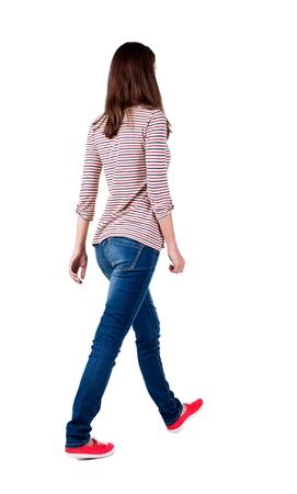 Zurück zu Fuß Frau in Jeans. schöne Brünette Mädchen in Bewegung. Rückansicht der Person. Rückansicht Menschen Kollektion. Isolierte über weißem Hintergrund. Das Mädchen in einem gestreiften T-Shirt mit Ärmeln podkatannymi geht voran