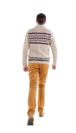 striding: Back view of going  handsome man in a knitted sweater. walking young guy . Rear view people collection.  backside view of person.  Isolated over white background. Stock Photo