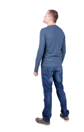 to stand: Back view of young man in t-shirt and jeans  looking.   Standing young guy. Rear view people collection.  backside view of person.  Isolated over white background.