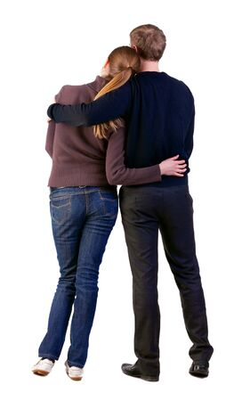 Back view of young couple (man and woman) hug and look into the distance. beautiful friendly girl and guy together. Rear view. Isolated over white background. Stock Photo