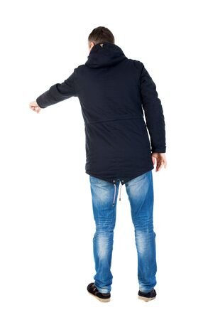 parka: Back view of pointing man in winter jacket  looking up.   Standing young guy in parka. Rear view people collection.  backside view of person.  Isolated over white background. A guy in a black jacket with a hood is pointing far down. Stock Photo
