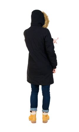 fur hood: Back view of  pointing young women in parka. Young girl gesture. Rear view people collection.  backside view of person.  Isolated over white background. The girl in a jacket with a fur hood presses.  Stock Photo