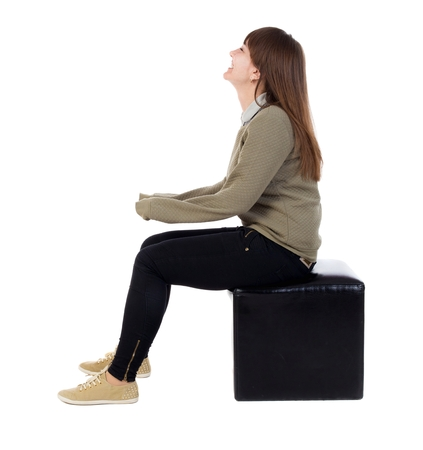 back view of young beautiful  woman sitting.  girl  watching. Rear view people collection.  backside view of person.  Isolated over white background. The girl is sitting on a leather ottoman and smiling.
