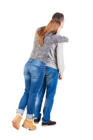 on tiptoes: Back view of young embracing couple (man and woman) hug and look into the distance. beautiful friendly girl and guy together. Rear view people collection.  backside view of person.  Isolated over white background. Girl standing on tiptoes and hugs from be Stock Photo
