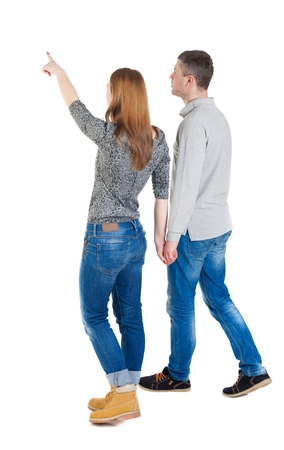 Back view of walking young couple (man and woman) pointing. Rear view people collection. backside view of person. Isolated over white background The girl holding the hand of Man, and shows his hand forward. photo