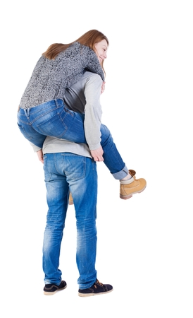 Back view of young embracing couple (man and woman) hug and look into the distance. beautiful friendly girl and guy together. Rear view people collection.  backside view of person.  Isolated over white background. Man carries in her arms the girl. photo