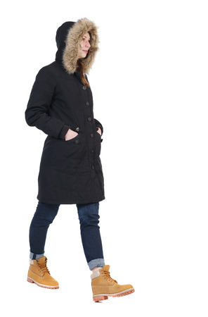 back view of walking  woman in winter jacket with hood. beautiful brunette girl in motion.  backside view of person.  Rear view people collection. Isolated over white background. his hands in the pockets of the girl goes to the right. photo