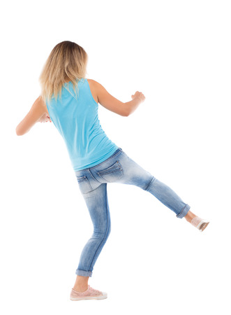 wimp: skinny woman funny fights waving his arms and legs. Isolated over white background. Blonde gets lower kick.
