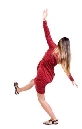 balances: Balancing young woman.  or dodge falling woman. Rear view people collection.  backside view of person.  Isolated over white background. The girl in red plaid dress balances trying not to fall. Stock Photo
