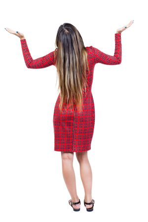 appeals: back view of woman. Young woman in vest presses down on something. Isolated over white background. Rear view people collection. backside view of person. The girl in red plaid dress appeals to God.