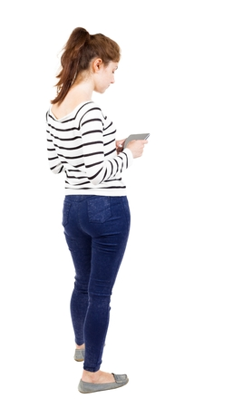 bent over: back view of standing young beautiful  girl with tablet computer in the hands of. girl  watching. Rear view people collection.  backside view of person.  Isolated over white background. Girl in white striped jacket bent over the plate Stock Photo