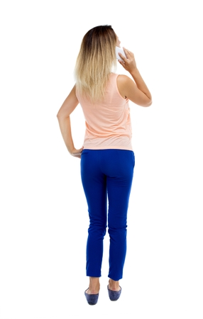 looking back: back view of a woman talking on the phone.  backside view of person.  Rear view people collection. Isolated over white background. Blonde in blue trousers pressed to his ear listening to the phone. Stock Photo