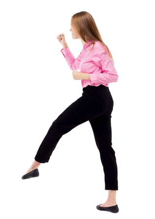 wimp: skinny woman funny fights waving his arms and legs. Isolated over white background. Woman office worker in a pink shirt has the right foot.