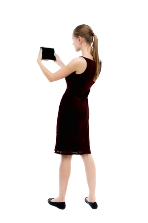 girl in burgundy dress: back view of standing young beautiful  girl with tablet computer in the hands of. girl  watching. Rear view people collection.  backside view of person.  Isolated over white background. The blonde burgundy dress holding to a horizontal smartphone.