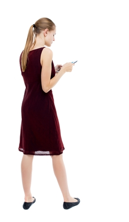 girl in burgundy dress: back view of standing young beautiful  girl with tablet computer in the hands of. girl  watching. Rear view people collection.  backside view of person.  Isolated over white background. The blonde burgundy dress standing left side and looking at the table