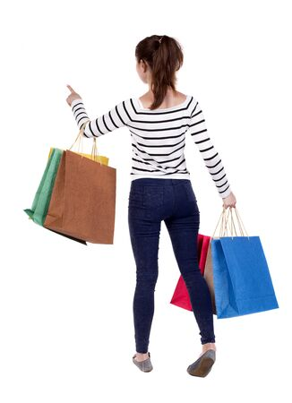 back posing: back view of woman  with shopping bags pointing . beautiful brunette girl in motion.  backside view of person.  Rear view people collection. Isolated over white background. Girl in white striped sweater holding purchases in hand and presses the elevator b