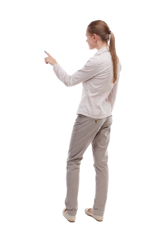 side view: Back view of  pointing woman. beautiful girl. Rear view people collection.  backside view of person.  Isolated over white background.  A girl in a white jacket is pointing into the distance.