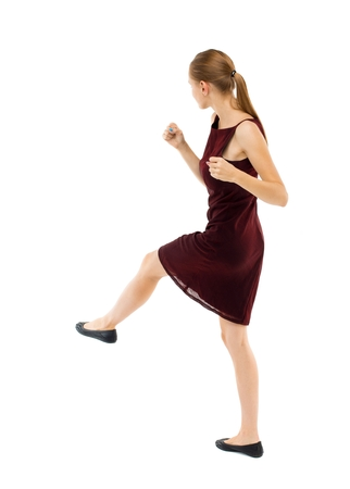 girl in burgundy dress: skinny woman funny fights waving his arms and legs. Isolated over white background. Blonde girl in a burgundy dress has foot.