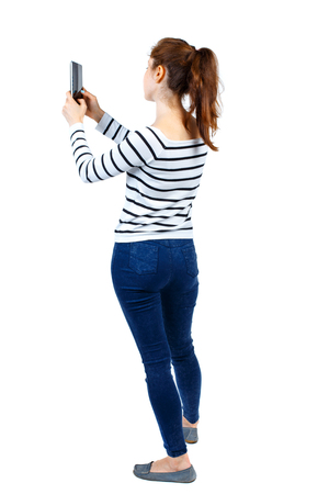 back view of standing young beautiful  woman  using a mobile phone. girl  watching. Rear view people collection.  backside view of person.  Isolated over white background. Girl in a striped sweater photographing something on the side of the tablet. Stock Photo