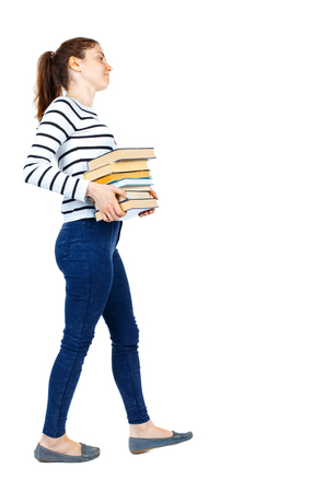 Girl comes with  stack of books. side view. Rear view people collection.  backside view of person.  Isolated over white background. Girl in a striped sweater goes to the side while holding heavy books.